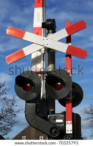 Railway crossing sign with lights underneath.  This is for a road traffic and to warn it of when a train is coming. The mechanics are set against a blue sky. - stock photo