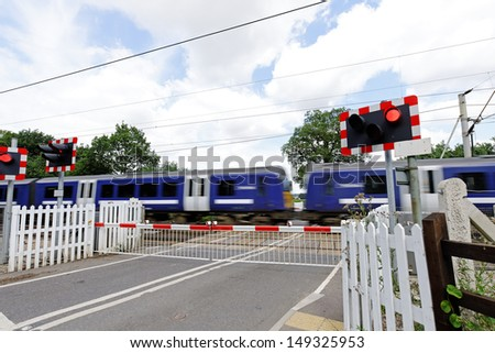 Railway crossing with passenger train at speed and barriers closed - stock photo