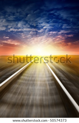 Railway in motion blur at sunset. - stock photo