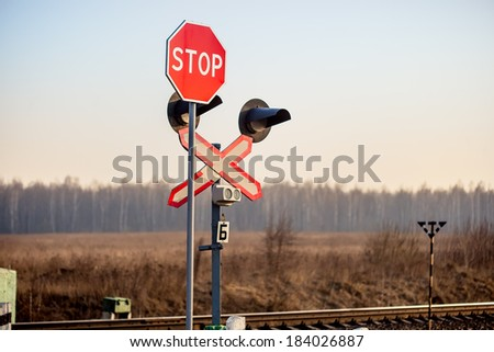 """Railway level crossing with warning sign """"Stop"""" - stock photo"""