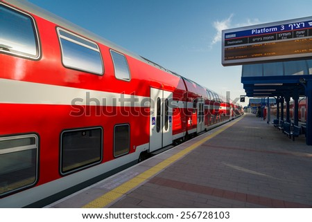Railway station and modern red train - stock photo