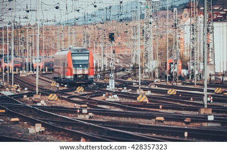 Railway station with modern red commuter train at sunset in Nuremberg, Germany. Railroad with vintage toning - stock photo