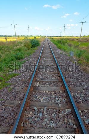 railway to horizon under cloudy sky - stock photo