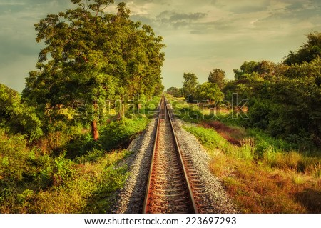 Railway track crossing rural landscape under evening sunset sky. Travel concept in vintage hipster style - stock photo