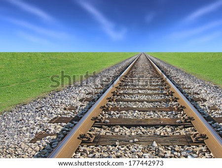 Railway track, green grass and blue sky on the horizon - stock photo
