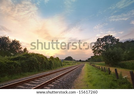 railway track in a rural landscape with sunset in the back - stock photo