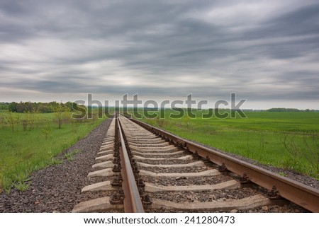 Railway track in the field on the cloudy day  - stock photo