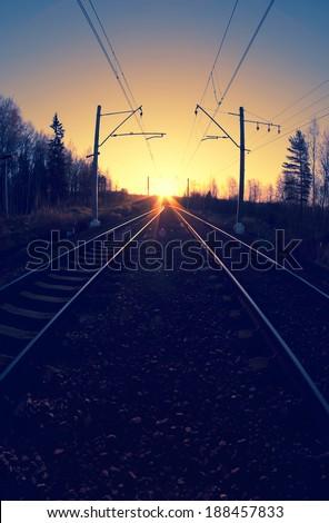 railway tracks at sunset, cross-processing effect - stock photo