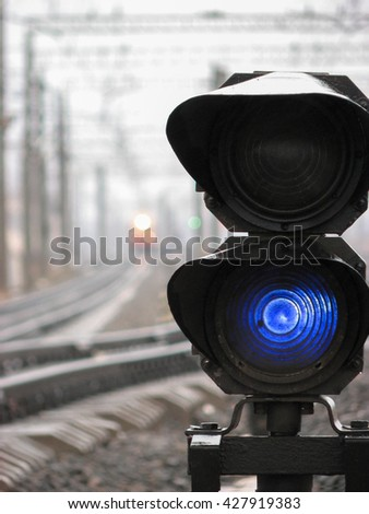 Railway traffic light shows blue signal on railway. Blue light. Moving train with lights and green railway traffic light are on the background - stock photo
