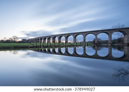 Railway viaduct, no train - the Arthington Viaduct and the mirror calm River Wharfe in West Yorkshire - stock photo