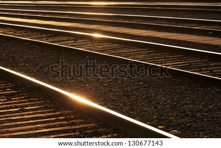 Railways sleepers and stones with sheens of the sun on the rails. - stock photo