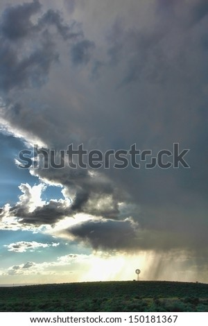 Rain and storm clouds over a ranch with a windmill - stock photo
