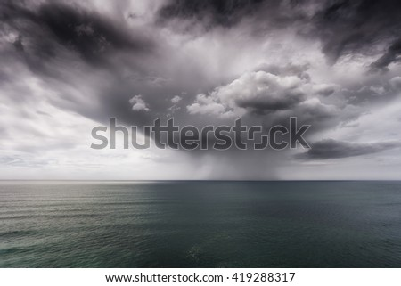rain and stormy cloud on the sea - stock photo