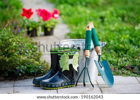 Rain boots and garden equipments on the path - stock photo