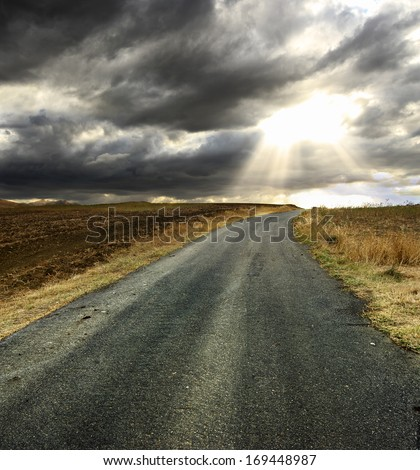 rain clouds over rural road landscape - stock photo