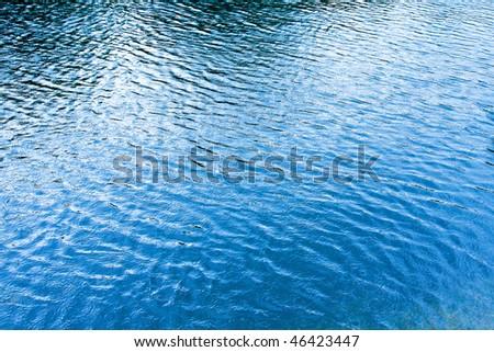 Rain drops at blue lake water surface - stock photo