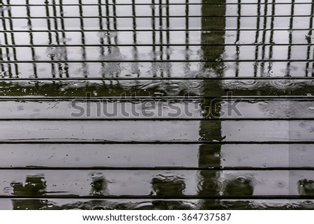 Rain drops dripping / splashing to wooden deck. Forming abstract designs and patterns against vertical bars, with selective focus. For abstract, vintage, grunge, weathered, backgrounds and textures. - stock photo