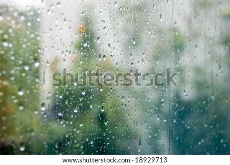 Rain drops on a window, blurry background. - stock photo