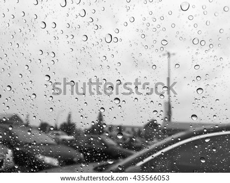 rain drops on car window in black and white - stock photo