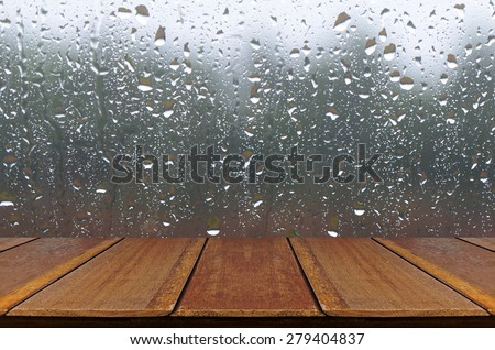 Rain Drops on Glass Window Background with Wood Table. - stock photo