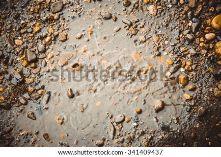 Rain drops on the stony earth - stock photo