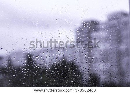 Rain drops on the window in the big city. Big building on the background. - stock photo