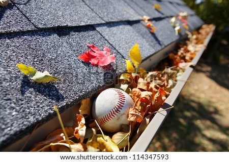 Rain gutter full of autumn leaves with a baseball - stock photo