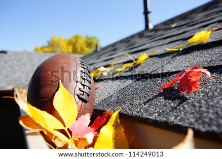 Rain gutter full of autumn leaves with a football - stock photo
