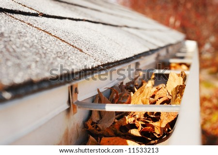 Rain Gutter full of fallen leaves - stock photo