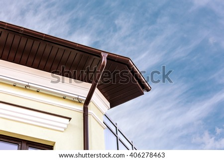 rain gutter on house with dark blue sky in the background - stock photo