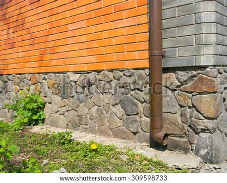 Rain gutter without any drainage systems near house foundation. Bad example. - stock photo