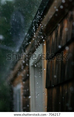 Rain hitting hard, splashing off a roof. High speed photography freezing droplets in mid air. - stock photo