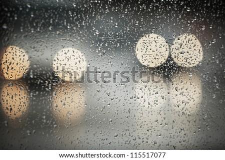 Rain in the city - selective focus on the raindrop - stock photo