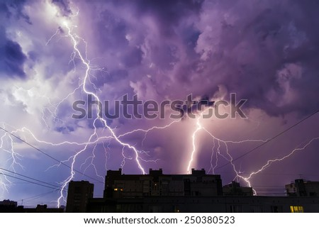 Rain, lightning, shot in the city over the houses. - stock photo