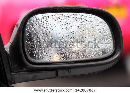 Rain on a car mirror - stock photo