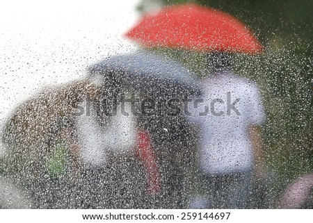 Rain on a window looking out to people in a street scene - stock photo