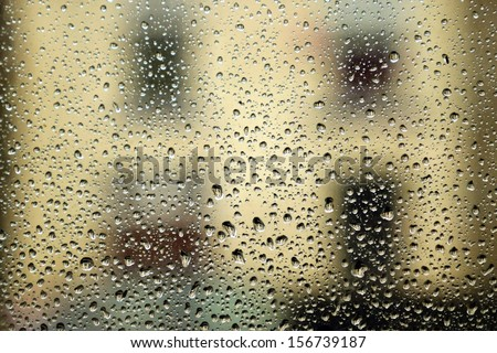 Rain on window with house in distance. - stock photo