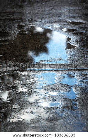 rain puddles on the pavement in the city - stock photo