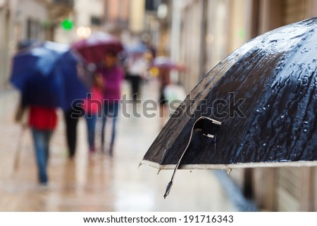 rain umbrella and walking people in the rainy city in the blurred background - stock photo