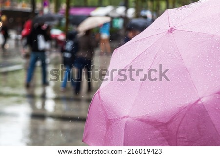 rain umbrella with blurred people in the background  - stock photo