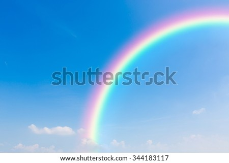 Rainbow and blue sky background. - stock photo