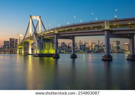 Rainbow bridge at night with Tokyo tower in background - stock photo