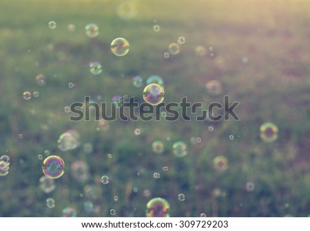 Rainbow bubbles from the bubble blower,vintage background. - stock photo