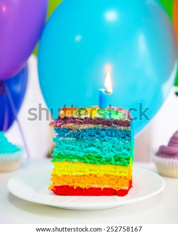 Rainbow cake decorated with birthday candle. Balloons on the background - stock photo
