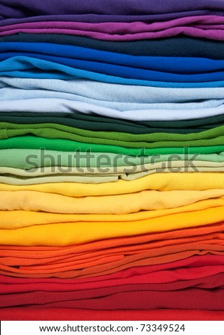 Rainbow clothes background. Pile of bright folded clothes. - stock photo