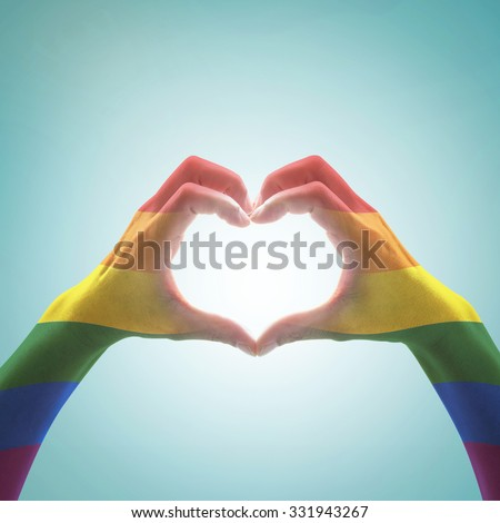 Rainbow color flag pattern on woman human hands forming in heart shape on blue vintage tone background: Symbolic equal rights in love same marriage social equality of LGBT community/ people concept    - stock photo