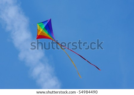 rainbow colored kite flying below an aircraft vapor trail - similar image with clear blue sky also available - stock photo