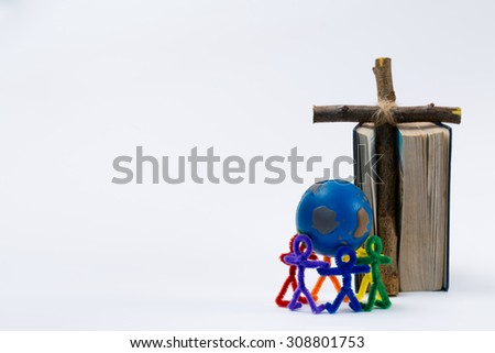 Rainbow colored people hold the world while a Bible and cross are in the background. This would be a nice photo for any educational purposes of telling people of all cultures about the Bible. - stock photo