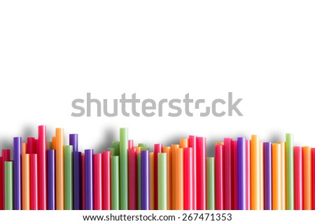 Rainbow colored plastic drinking straws background pattern arranged as a line border at the bottom of the frame with copy space over white - stock photo