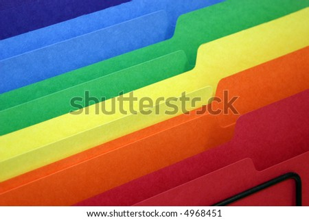 rainbow colored tabbed file folders in a basket - stock photo